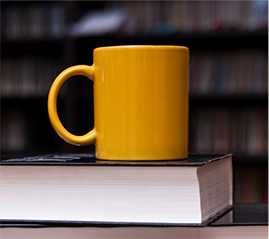 Coffee cup on top of school books, in a library at a university in Calgary, Alberta