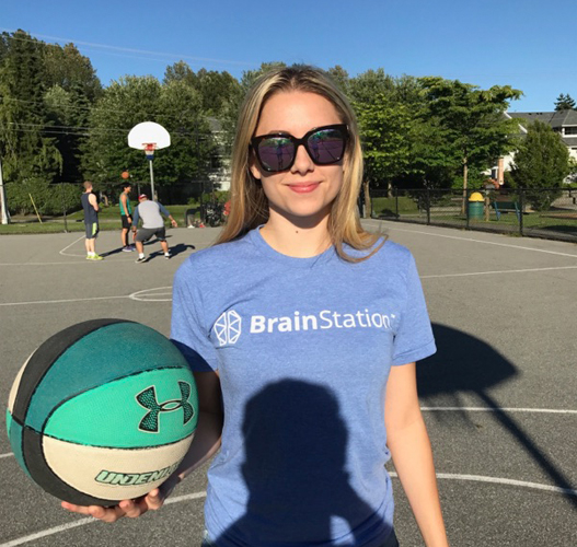 girl in brainstation t-shirt playing basketball